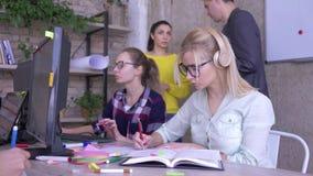 Ludzie przy pracą, potomstwo drużyna pracują w nowożytnym biurze na plan biznesowy dziewczyny spojrzeniach przy kamerą i one uśmi zbiory wideo