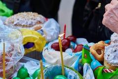 Ludzie przychodzący kościół uświęcać Wielkanocnych torty i jajka zaświecających kościelne świeczki, Obraz Royalty Free