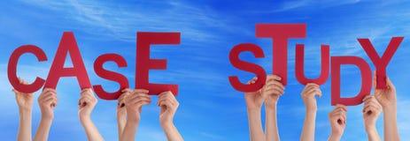 Ludzie ręk Trzyma Czerwonego słowa badania przypadków niebieskie niebo Fotografia Stock