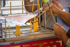 Ludzie ręk zaświeca kadzidłowego kija ogienia od świeczki use dla fotografia stock