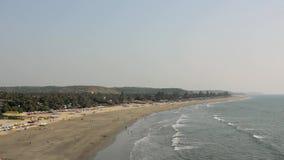 Ludzie relaksują na piaskowatym wybrzeżu z, kąpać w ocean falach i, widok z lotu ptaka słońce parasolami i łóżkami zbiory wideo