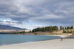 Ludzie relaksuje Jeziornym Tekapo, Południowa wyspa Nowa Zelandia, z tęczami w niebie Obrazy Royalty Free