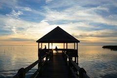 Ludzie relaksuje na molu na jeziorze przy zmierzchem Obrazy Stock