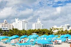 Ludzie relaksuje na pokładów krzesłach pod błękitnymi parasolami Zdjęcie Stock