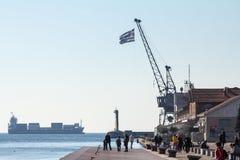 Ludzie relaksuje na quay - molo stary port Saloniki, grek flaga i ładunku statek, może widzieć w tle obrazy royalty free