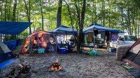 Ludzie relaksuje w kolorowej obóz ziemi wokoło ogienia z namiotami, samochodami dostawczymi & pojazdami w lesie w Ginnie, Skaczą obrazy royalty free