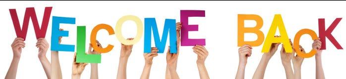 Ludzie ręk Trzyma Kolorowego słowa powitanie Z powrotem Fotografia Stock