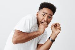 Ludzie ` s emocj Zakończenie up młody przystojny ciemnoskóry amerykański facet z afro uczesaniem w białych koszulki mienia rękach Obrazy Stock