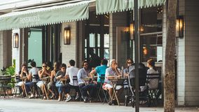 Ludzie siedzą na zewnątrz pobliskiej kawiarni obraz royalty free