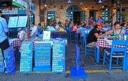 Ludzie siedzą w chodniczek ulicznej kawiarni w Chania nabrzeżu na Crete Obrazy Stock