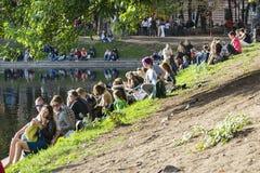 Ludzie Siedzą na trawie w parku Zdjęcie Stock