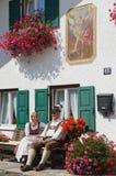 Ludzie siedzą przed tradycyjnym bavarian domem w Mittenwald, Niemcy Fotografia Stock