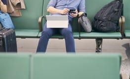 Ludzie siedzi i pracuje na pastylce gdy czekać na opóźniającego lot zdjęcia stock