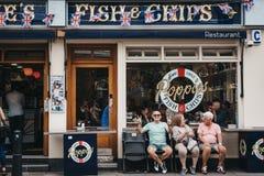 Ludzie siedzi na ławce na zewnątrz Poppie układów scalonych & ryby robią zakupy w Londyn, UK obraz stock