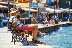 Ludzie siedzi na ławce w starym schronieniu Chania na Crete, Grecja Zdjęcie Stock