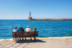 Ludzie siedzi na ławce w starym schronieniu Chania na Crete, Grecja Zdjęcia Royalty Free
