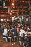 Ludzie siedzi ulicznego jedzenie i je przy wieczór Świątynnym Ulicznym rynkiem w Hong Kong obrazy stock