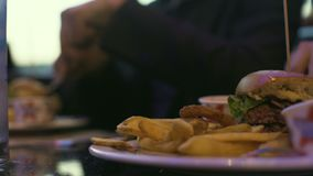 Ludzie siedzi w kawiarni komunikuje kaloria hamburger z francuskimi dłoniakami i je zdjęcie wideo