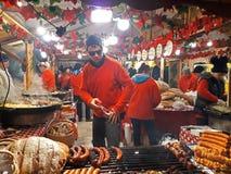 Ludzie smażą piec na grillu kiełbasy na dużym obwieszenie grillu przy boże narodzenie rynkiem Obraz Stock