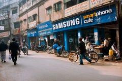 Ludzie spaceru za telefonów komórkowych sklepami Obraz Royalty Free