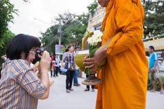 Ludzie stawiać karmowych ofiar w mnicha buddyjskiego datkach rzucają kulą dla lepidła Obraz Stock