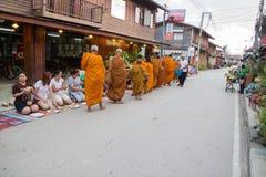 Ludzie stawiać karmowych ofiar w mnicha buddyjskiego datkach rzucają kulą dla lepidła Fotografia Royalty Free