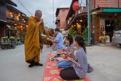 Ludzie stawiać karmowych ofiar w mnicha buddyjskiego datkach rzucają kulą dla lepidła Obrazy Royalty Free