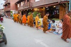 Ludzie stawiać karmowych ofiar w mnicha buddyjskiego datkach rzucają kulą dla lepidła Obraz Royalty Free
