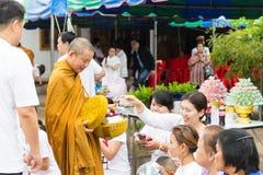 Ludzie stawiać karmowych ofiar w mnicha buddyjskiego datkach rzucają kulą dla Vir Obraz Stock