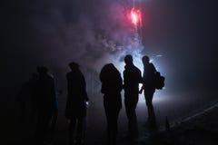 Ludzie stoi fajerwerki i ogląda, silvester, zmrok, sylwetka Fotografia Royalty Free