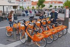 Ludzie stoją przy rowerowym do wynajęcia punktem przy urzędu miasta kwadratem w Vilnius, Lithuania Zdjęcia Royalty Free