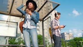 Ludzie stoj? przy autobusow? przerw? z telefonami komórkowymi Czekać na miasto autobus zbiory wideo