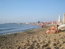 Ludzie sunbathing, kąpać się w morzu lub zbiera skorupy na plaży w lato ranku, Obraz Royalty Free