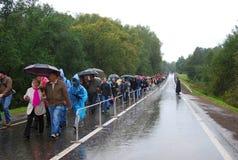 Ludzie tłoczą się spacer pod parasolami na mokrej drodze Zdjęcia Royalty Free