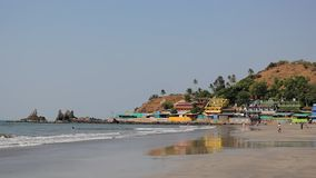 Ludzie turystów chodzą wzdłuż piaskowatej plaży i kąpać w falach ocean przeciw tłu jaskrawi kolorowi budynki zbiory