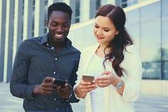 Ludzie używa smartphones nad nowożytnym budynkiem obraz stock