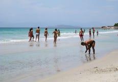 Ludzie w bielu wyrzucać na brzeg z błękitnym krystalicznym morzem w lecie przy nakrętką Zdjęcia Stock