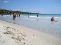 Ludzie w bielu wyrzucać na brzeg z błękitnym krystalicznym morzem w lecie przy nakrętką Obraz Royalty Free