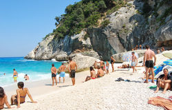 Ludzie w bielu wyrzucać na brzeg z błękitnymi krystalicznymi fala w summert i morzem Zdjęcie Stock