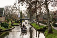 Ludzie w dwa małych łódkach pływa statkiem na wąskich kanałach wśród budynków w sławnej wiosce Giethoorn fotografia stock