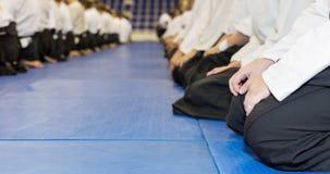 Ludzie w kimona i hakama obsiadaniu na tatami na sztuk samoobrony trenować Zdjęcie Stock