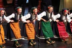 Ludzie w tradycyjnych folklor?w kostiumach wykonuj? ludowego tana Bu?garski Horo zdjęcia stock