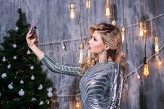 Ludzie, wakacje, boże narodzenia i technologii pojęcie, - piękna seksowna kobieta w wieczór sukni bierze selfie obrazek smartphon fotografia royalty free