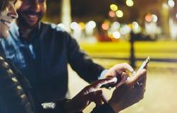 Ludzie wpólnie wskazuje palec na parawanowym smartphone na tła bokeh świetle w nocy atmosferycznym mieście, grupowi dorosli modni obrazy stock