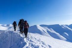 Ludzie wycieczkuje w śniegu przy Vardousia górami w Środkowej Grecja E4 ścieżce zdjęcia stock