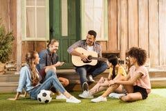 Ludzie wydaje czas wpólnie, uśmiechnięty mężczyzna bawić się gitarę podczas gdy inny przyjaciół słuchać zdjęcia stock