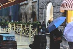 Ludzie z parasolami w deszczu w starym miasteczku głębokość pola płytki Ostrość na parasolu obraz stock