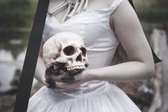 Ludzka czaszka w przerażających pann młodych rękach pojęcie kalendarzowej daty Halloween gospodarstwa ponury miniatury szczęśliwa zdjęcie royalty free