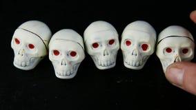 Ludzka ręka stawia jeden białych czekoladowych cukierki w zredukowanym czaszka kształcie zbiory