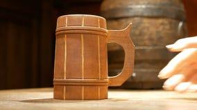 Ludzka ręka stawia starego drewnianego piwnego kubek na stole na tle mała baryłka dla napojów Naczynia w pubie zbiory